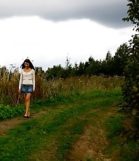 Babe tinkles on a road in the middle of a field