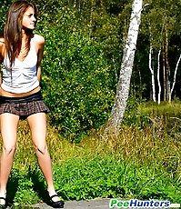 Cute young chick in checkered mini pisses outdoors